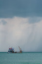 Raining one fisherman boat in the sea with cloud Royalty Free Stock Photography