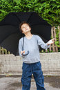 Is it raining a teenage boy outside holding a black umbrelaa over him he holding his left hand out to feel whether Royalty Free Stock Photo