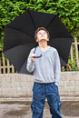 Is it raining a teenage boy outside holding a black umbrelaa over him he looking up to see whether Royalty Free Stock Photography
