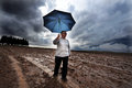 Rainstorm negba isr oct person holds umbrella in the field during on oct the globally averaged annual precipitation over land is Stock Photos