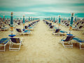 Rainy beach season empty scenery with deckchairs and umbrellas Royalty Free Stock Image