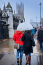 Rainy day in london two women are walking and hiding under an umbrella a Royalty Free Stock Photos