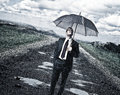 Rainy day and man with umbrella on road Stock Photos