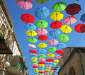 Rainy day protection with flying umbrellas in a summer street festival Royalty Free Stock Photo