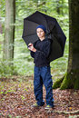 Rainy day a teenage boy standing in a forest holding an umbrella Royalty Free Stock Images