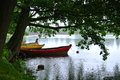 Rainy day at Trakai natural park, a view to a lake, old big trees and fishing boats for rent decorated with different colors Royalty Free Stock Photo