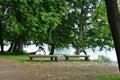 Rainy day at Trakai natural park, a view to a lake, old big trees, wooden benches and a fishing boat Royalty Free Stock Photo