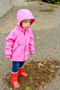 Rainy weather toddler girl standing in puddle Royalty Free Stock Images