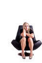 Raised eyebrows pretty caucasian girl sitting on a big black chair resting her arms on her knees and holding her head with on a Royalty Free Stock Image