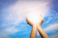 Raised hands catching sun on blue sky. Concept of spirituality,