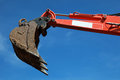 Raised scoop of an earth mover over blue sky Stock Images