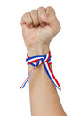 Raised up clenched fist with tricolor stripes wrist band isolated on white Royalty Free Stock Image