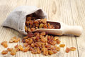 Raisin in a sack and spoon on wooden table Stock Photo