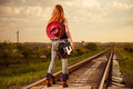 Raiway to horizon woman in jeans with guitar at countryside railway Stock Images