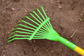 Rake a close up view of a metal green and yellow yard Royalty Free Stock Photography