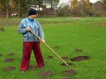 Raking molehills senior country farmer smooth by rake Stock Photography