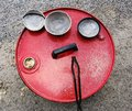 Raku ceramics three bowls obtained with the technique resting on a lid of a bright red color and the relative gripper to be Royalty Free Stock Photos