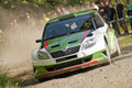 Rally car in action Å¡koda fabia s competition on gravel with dust Royalty Free Stock Images