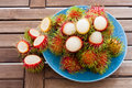 Rambutan in blue dish background image of many peel on the wood slat Royalty Free Stock Image