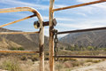 Ranch gate is locked and chained with mountains and brush in the background Royalty Free Stock Image