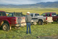 Rancher and cowboy looking at pickup trucks in centennial valley near lakeview mt Royalty Free Stock Photo