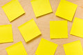 Randomly arranged yellow post it collection overhead shot of square blank notes glued on wooden board and ready to take a note Stock Photos