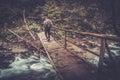 Randonneur marchant au dessus du pont en bois dans une forêt Photographie stock