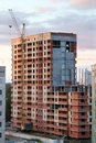 сrane and building under construction of yellow and red brick in evening Stock Photo