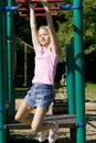 Rapariga que joga em barras de macaco no parque Fotos de Stock Royalty Free