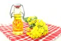 Rapeseed oil a bottle of and flowers against white background Stock Photography