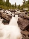 Rapid stream flowing down over stones  Blurred waves of stream running over boulders and stones, high water level after rains Royalty Free Stock Photo