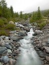 Rapid stream flowing down over stones blurred waves of stream running over boulders and stones high water level after rains heavy Royalty Free Stock Images