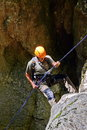 Rappelling climber a a stone wall belay device Stock Photo