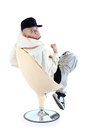 Rapper sits on chair with back to camera Stock Photos