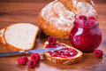 Rapsberry jam with slice of bread on wooden table Royalty Free Stock Photography