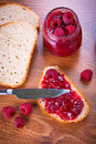 Rapsberry jam with slice of bread on wooden table Stock Photography