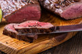 Rare roast beef sirloin on cutting board Royalty Free Stock Photos