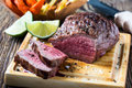 Rare roast beef sirloin with french fries and slices baked pumpkin chips on cutting board Stock Photo