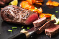 Rare roast beef sirloin with slices baked pumpkin chips on gray board Stock Photo