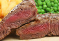 Rare sirloin beef steak juicy char grilled to medium and served with chips peas Stock Photos