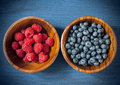 Raspberries and blueberries in a wooden bowl of on blue vintage background Royalty Free Stock Photos