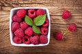 Raspberries in bowl on wooden table background top view Royalty Free Stock Photo