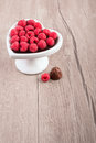 Raspberries in chocolate sauce on wood heart shaped plate of a wooden table text space Royalty Free Stock Image
