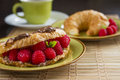 Raspberries french breakfast with croissant coffee and Royalty Free Stock Photo