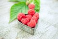 Raspberries in heart on old wooden table Royalty Free Stock Image