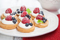 Raspberries mini cakes set of tasty with and blueberries on a white wooden table Stock Photo