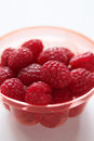 Raspberries in small red bowl close up narrow depth of field Royalty Free Stock Image