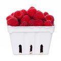 Raspberries in a white paper carton isolated on white Royalty Free Stock Photo