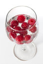 Raspberries in a wine glass with water Stock Images