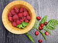 Raspberries in a wooden bowl on black wooden background Royalty Free Stock Image